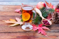 tea with lemon and cinnamon, ripe apples, red autumn leaves of m